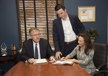 Image of Todd Torgersen, Anna Barbee Causey, and Reid Torgersen at a desk